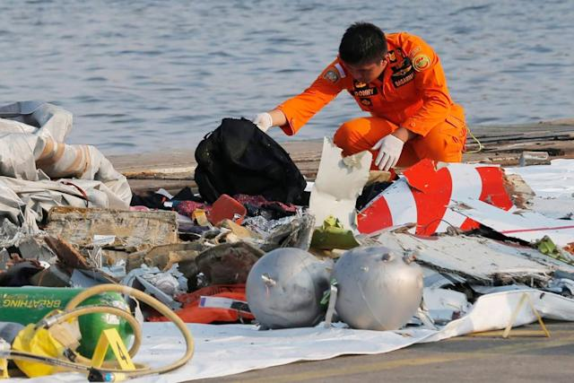 A member of Indonesian Search and Rescue Agency inspects debris from the Lion Air passenger jet that crashed off Java Island