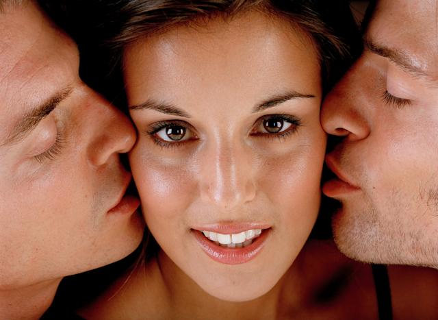 Young woman being kissed by two young men, close-up