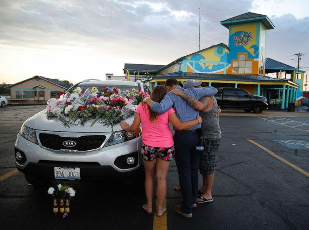 PHOTO: People pray by a car thought to belong to a victim of Thursday's boating accident before a candlelight vigil in the parking lot of Ride the Ducks, July 20, 2018, in Branson, Mo. (Charlie Riedel/AP)