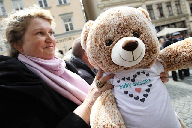 A well wisher holds a teddy bear wearing a t-shirt saying 'Baby Sussex' ahead of the arrival of Camilla, Duchess of Cornwall | Omer Messinger/Getty
