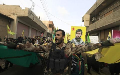 A member of the Kurdish People's Protection Units (YPG) takes part in a demonstration alongside Syrian-Kurds in the town of Amuda - Credit: AFP