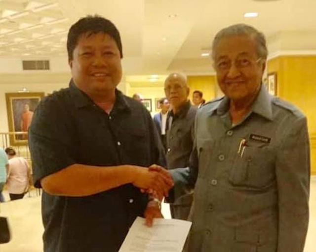 Johor PPBM Puteri Wangsa assemblyman and Tebrau chief Mazlan Bujang holding what is seen as an appointment letter together with Prime Minister Tun Dr Mahathir Mohamad at the prime minister's office in Putrajaya. — Picture viaFacebook/Kamal Hisham Jaafar