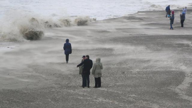 Hohe Wellen schlagen an den Strand von Wangerooge und nehmen den Sand mit.