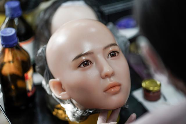 This photo taken on February 1, 2018 shows a worker painting the face of a silicone doll at a factory of EXDOLL, a firm based in the northeastern Chinese port city of Dalian. With China facing a massive gender gap and a greying population, a company wants to hook up lonely men and retirees with a new kind of companion: