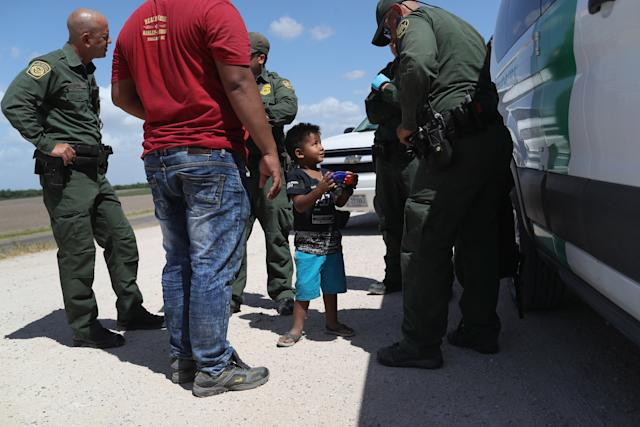 A boy and father from Honduras are taken into custody by U.S. Border Patrol agents near the U.S.-Mexico Border on June 12, 2018, near Mission, Texas. The asylum-seekers were then sent to a U.S. Customs and Border Protection (CBP) processing center for possible separation. (John Moore via Getty Images)