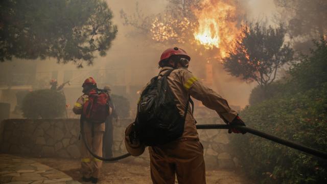 Feuerwehrleute bekämpfen einen Waldbrand in der Nähe von Athen. Foto: Eurokinissi