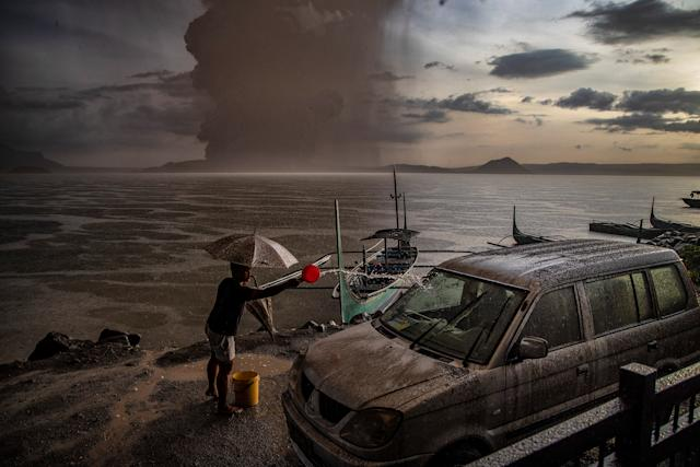 A resident in Talisay, in Batangas province, splashes water on a vehicle covered in ash mixed with rainwater as the Taal Volcano erupts on Jan. 12. | Ezra Acayan—Getty Images