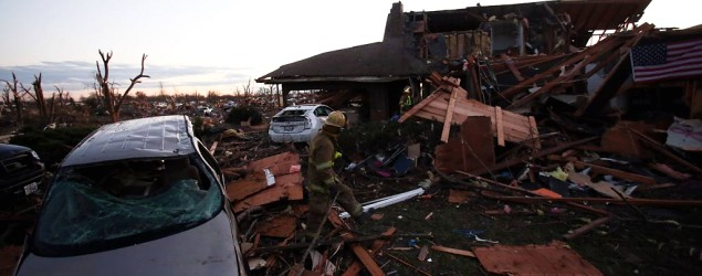 A firefighter searches through debris after a tornado struck on November 17, 2013 in Washington, Illinois. (Tasos Katopodis/Getty Images)