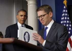 White House press secretary Jay Carney closes his briefing book as President Barack Obama makes a surprise visit to the Brady Press Briefing Room in Washington,...